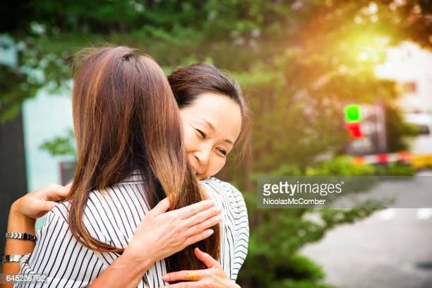 Mature Japanese woman hugs younger friend