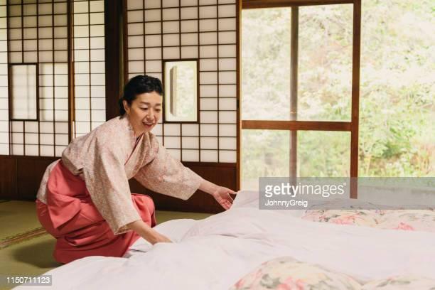 旅館の伝統的な旅館で布団を作る着物を着た成熟した日本人女性 - 旅館 ストックフォトと画像