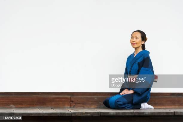 京都の寺院で瞑想でひざまずく伝統的な着物の成熟した日本人女性 - 優美 ストックフォトと画像