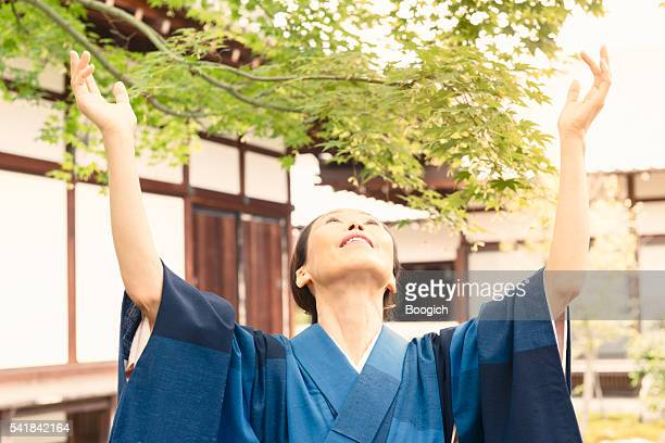 Mature Japanese Woman in Traditional Kimono Raises Hands in Joy