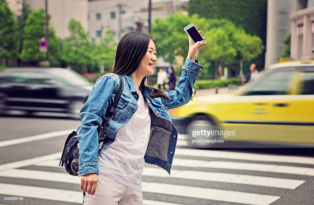 Mature Japanese woman is calling for taxi : Stock Photo