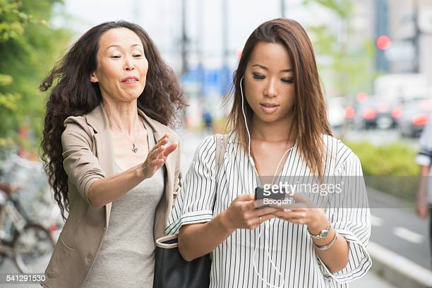 Mature Japanese Woman Running After Millenial Woman with Headphones