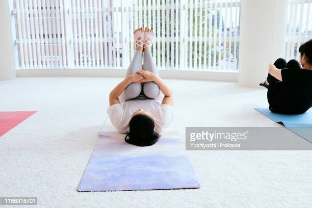 mature japanese women pilates in fitness studio - hugging knees stock pictures, royalty-free photos & images