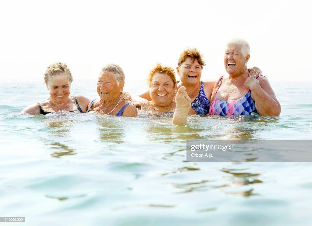 Mature ladies laughing on beach : Stock Photo