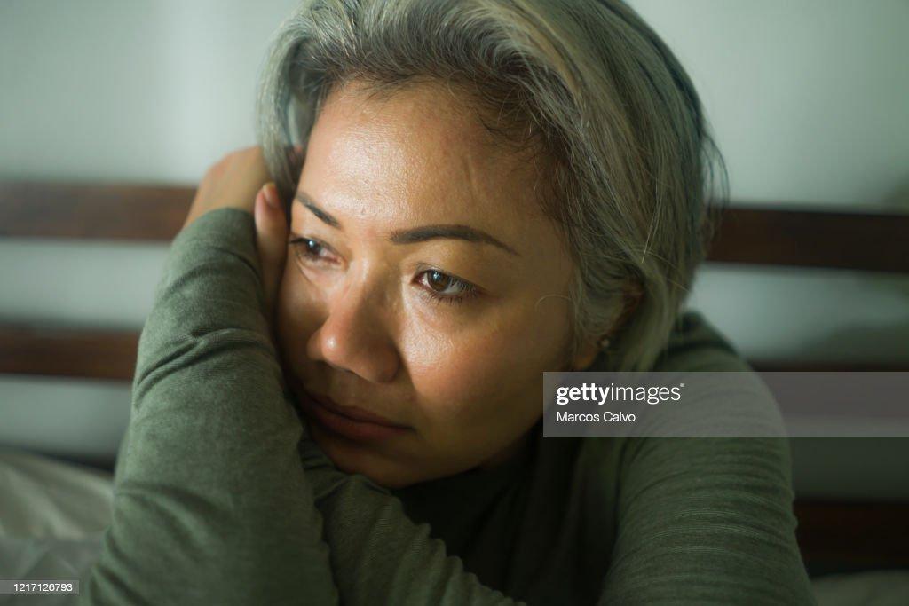 rijpe damecrisis - aantrekkelijke midden oude vrouw met grijs haar droevig en gedeprimeerd in bed dat bang en eenzaam het denken ongerust maakt over covid-19 viruspandemie tijdens huislockdown : Stockfoto