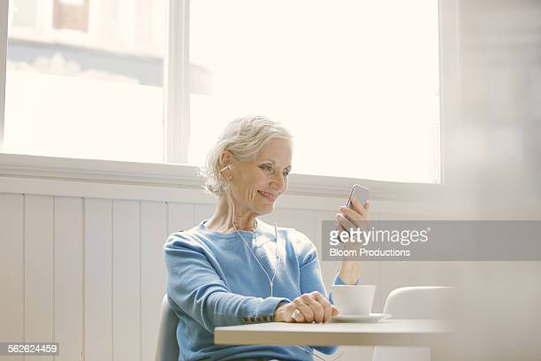 mature lady using a smart phone in a cafe - one senior woman only stock pictures, royalty-free photos & images