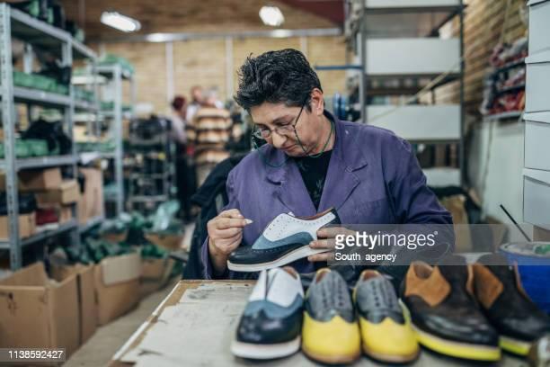 reife dame in der schuhfabrik - schuhmacher stock-fotos und bilder