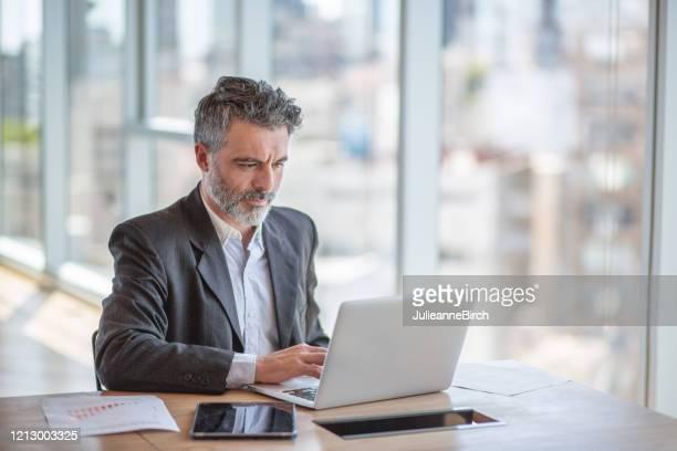reife lateinamerikanische geschäftsmann sitzt am schreibtisch mit laptop konzentriert sich auf die arbeit - finanzen und wirtschaft stock-fotos und bilder
