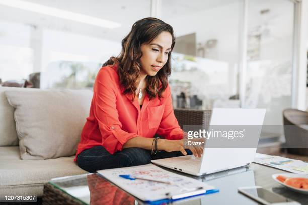 mature latin american businesswoman working from home - usare il laptop foto e immagini stock