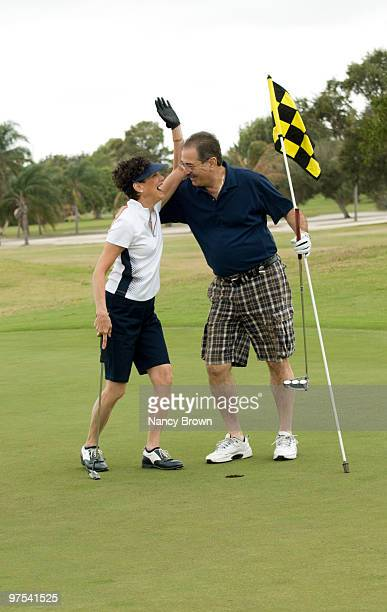 mature latin couple on golf course having fun. - celebration fl stock pictures, royalty-free photos & images