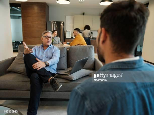homme latin mûr interviewant le jeune homme dans la salle de déjeuner - plan moyen angle de prise de vue photos et images de collection
