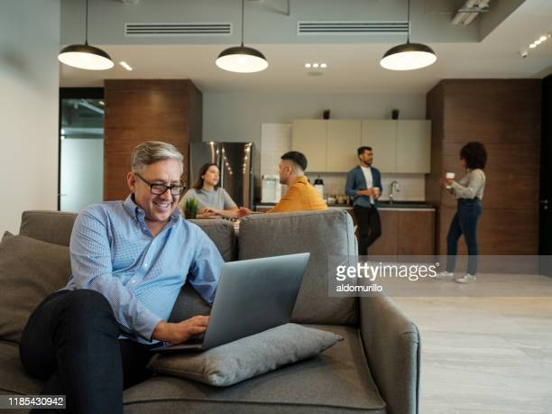 mature latin man using laptop in lunch room and smiling - medium shot stock pictures, royalty-free photos & images