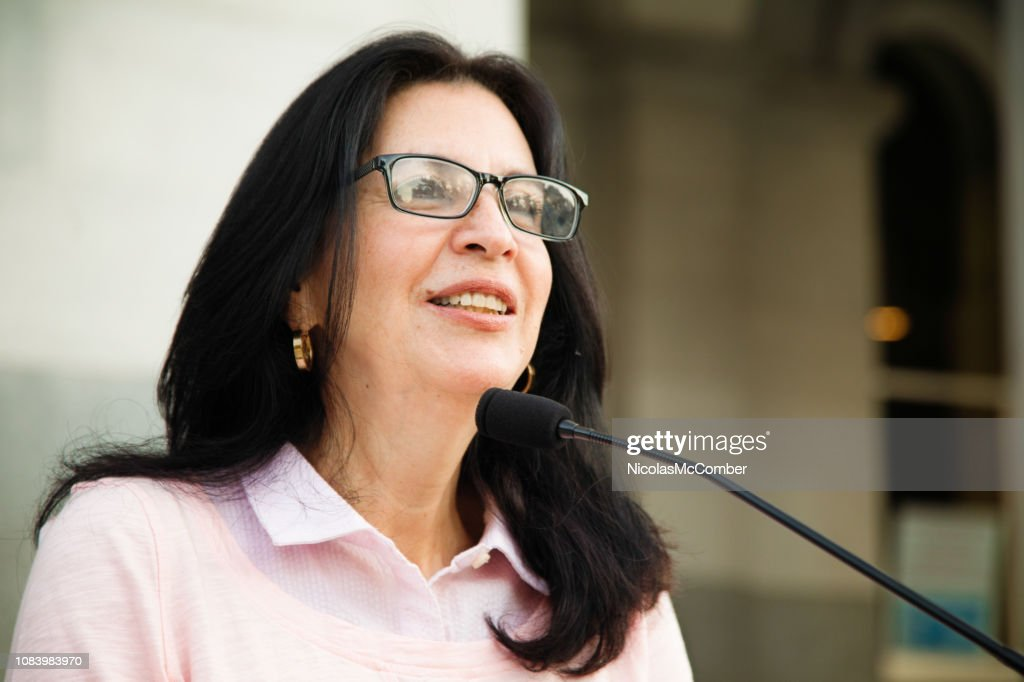 Mature Latina woman smiling at crowd during speech over microphone : Stock Photo