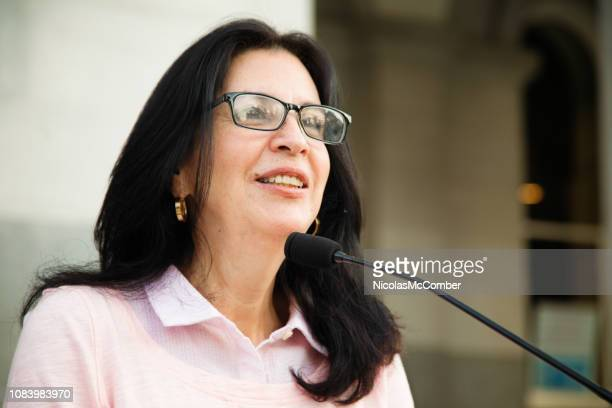 mature latina woman smiling at crowd during speech over microphone - women politics stock pictures, royalty-free photos & images