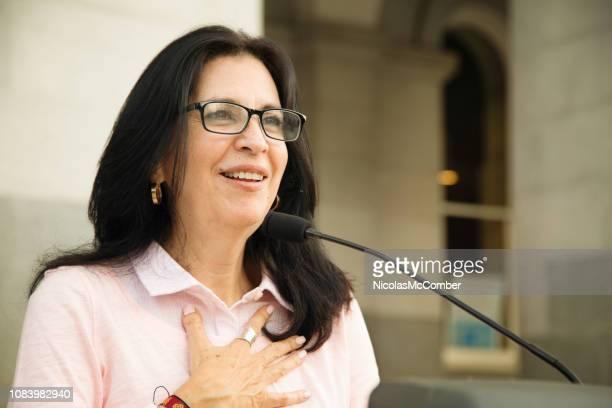 mature latina woman touched by crowd reaction during speech over microphone - politician stock pictures, royalty-free photos & images