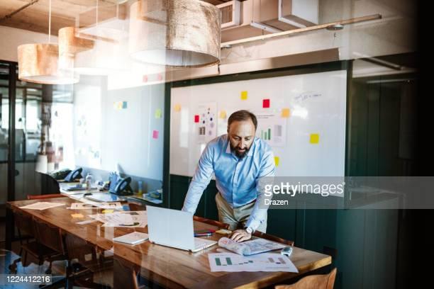 homme d'affaires latino mûr dans le bureau travaillant sur l'ordinateur portatif - professeur d'université photos et images de collection