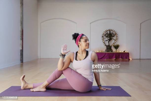 a mature latinx woman with curly dark hair, sits in a seated spinal twist, with a hindu god sculpture in the background of a yoga studio. - wellness stock pictures, royalty-free photos & images