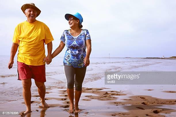 Mature laughing couple walking on the seashore