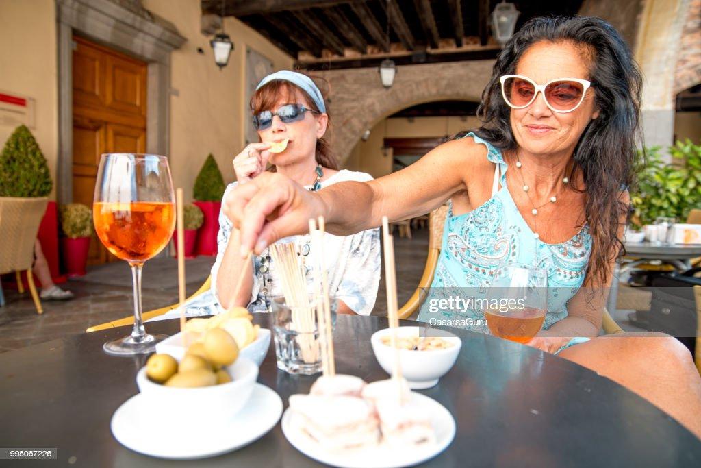 Mature Lesbian Couple Enjoying Snacks In A Bar Stock Photo
