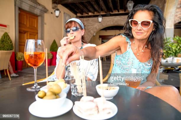 Mature Lesbian Couple Enjoying Snacks in a Bar