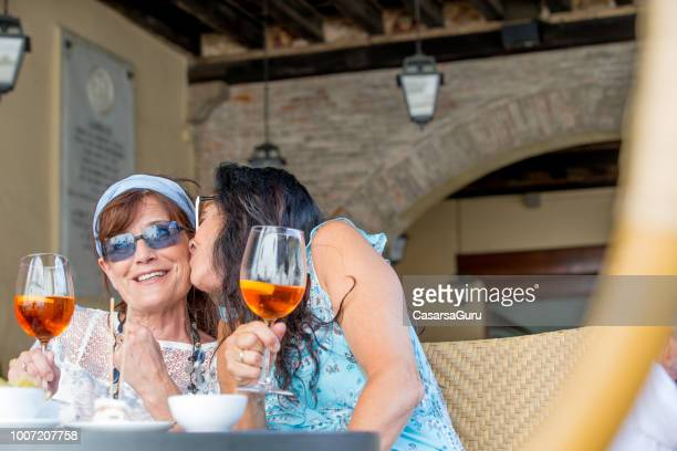 mature lesbian couple kissing on a date in a bar - lesbian dating stock pictures, royalty-free photos & images
