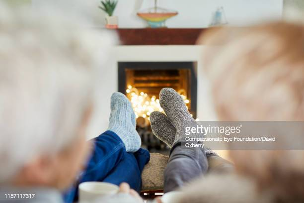 mature lesbian couple with hot drinks on living room sofa at fireside - hot wives photos stock pictures, royalty-free photos & images