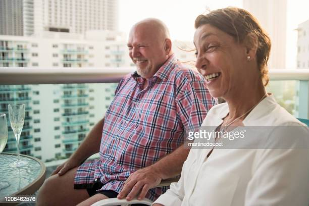 """mature lgbtq friends on a balcony at happy hour. - """"martine doucet"""" or martinedoucet stock pictures, royalty-free photos & images"""