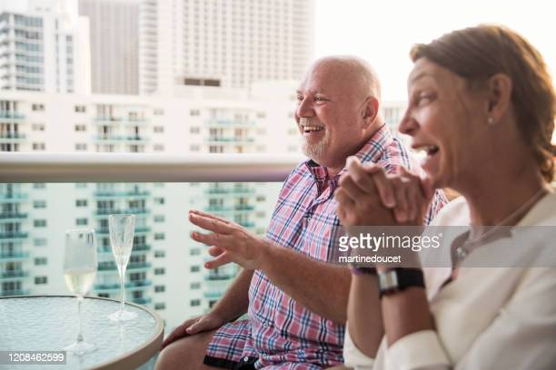 """mature lgbtq friends on a balcony at happy hour. - """"martine doucet"""" or martinedoucet foto e immagini stock"""