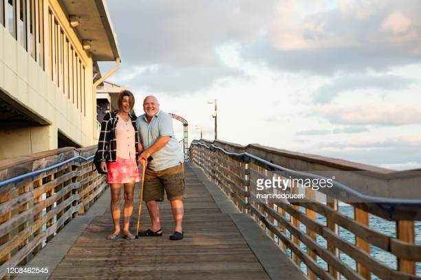 """mature lgbtq friends on a pier at sunset. - """"martine doucet"""" or martinedoucet stock pictures, royalty-free photos & images"""