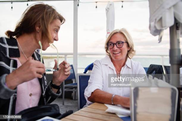 """mature lgbtq friends women on restaurant terrace. - """"martine doucet"""" or martinedoucet stock pictures, royalty-free photos & images"""