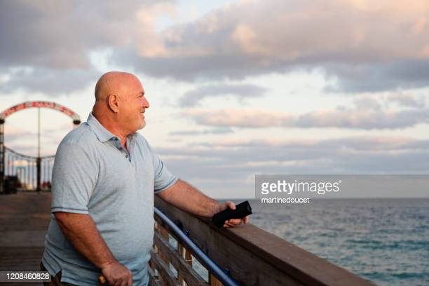 """mature lgbtq man on a pier at sunset. - """"martine doucet"""" or martinedoucet stock pictures, royalty-free photos & images"""