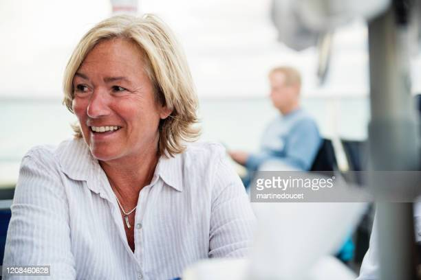 """mature lgbtq woman on restaurant terrace at happy hour. - """"martine doucet"""" or martinedoucet stock pictures, royalty-free photos & images"""