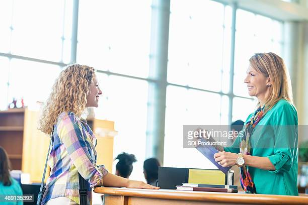 Mature librarian assisting student in high school or college library