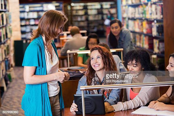 Mature librarian helps high school students in library