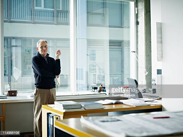 Mature male architect standing at desk in office