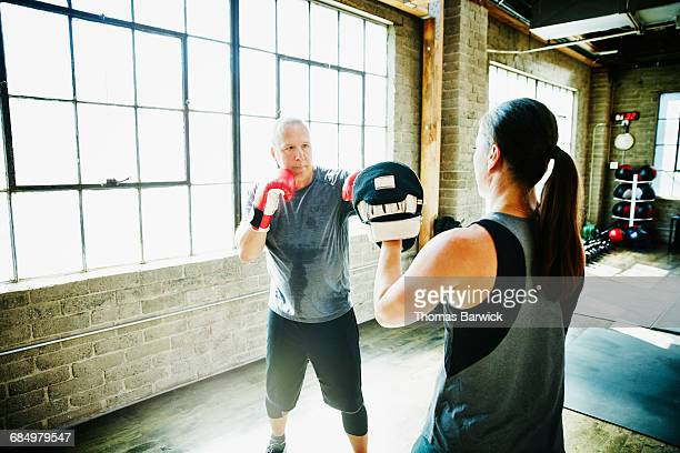 Mature male athlete boxing with coach in gym
