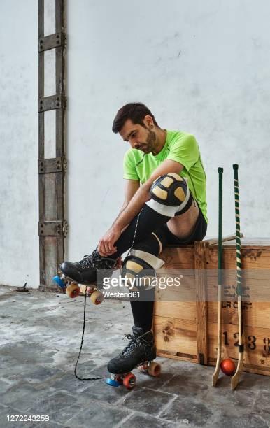 mature male athlete wearing roller skate while sitting by hockey sticks on wooden box against wall at court - caneleira roupa desportiva de proteção imagens e fotografias de stock