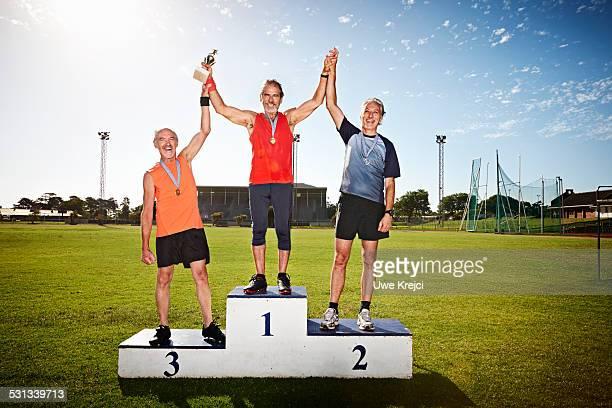 mature male athletes on winners podium - siegerpodest stock-fotos und bilder