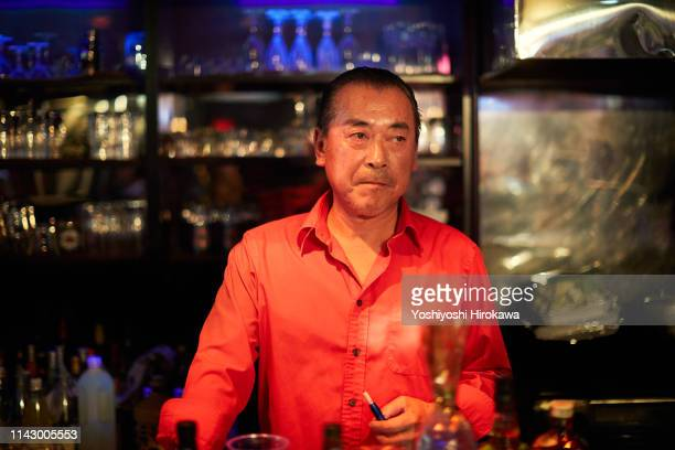 mature male bar owner standing at bar counter - オールバック ストックフォトと画像