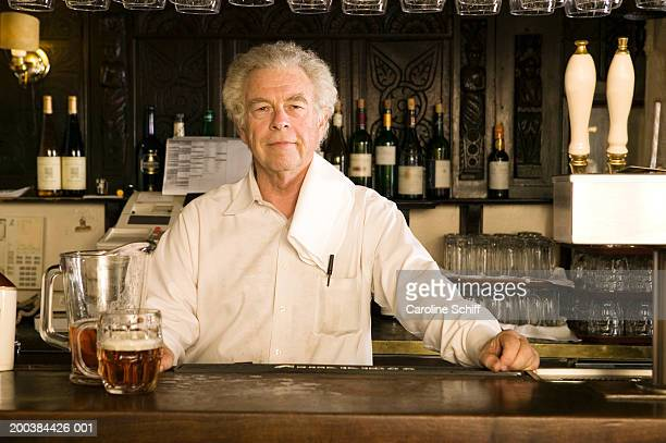 mature male bartender standing behind bar, smiling, portrait - wait staff stock pictures, royalty-free photos & images