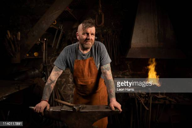 mature male blacksmith leaning against anvil in workshop, portrait - macho stock pictures, royalty-free photos & images