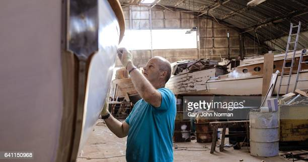 mature male boat builder working in workshop - shipyard stock pictures, royalty-free photos & images