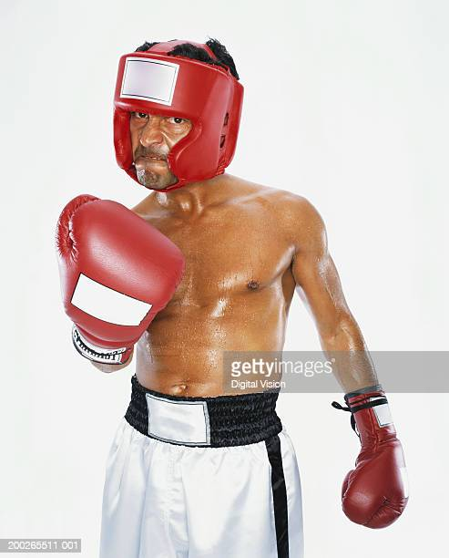 mature male boxer raising fist, portrait - one mature man only stock photos and pictures