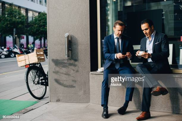 mature male business colleagues sitting with mobile phone and coffee cups on window sill at cafe - menschliche siedlung stock-fotos und bilder