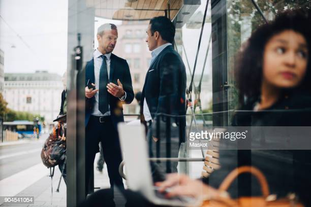 Mature male business coworkers talking while standing at bus stop seen from glass