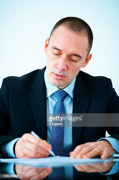 Mature male business entrepreneur in suit signing a document