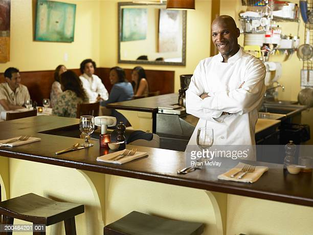 Mature male chef standing in restaurant, arms crossed, portrait