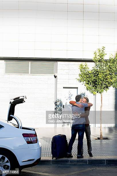 Mature male couple hugging next to car and suitcase