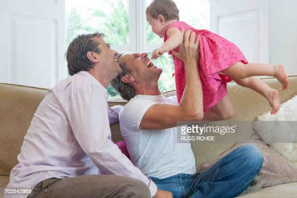 Mature male couple playing with baby daughter on sofa