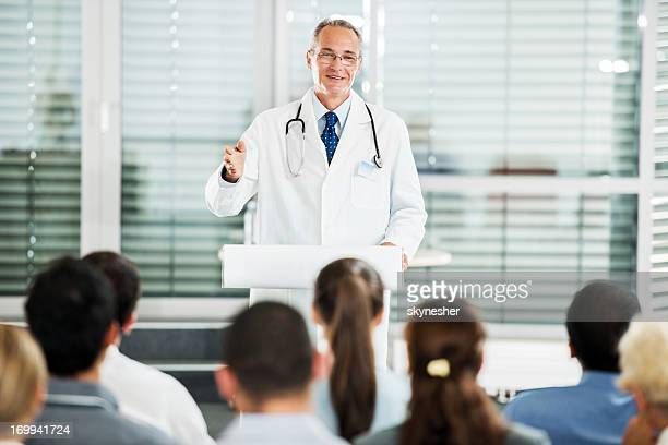 Mature male doctor giving a speech on seminar